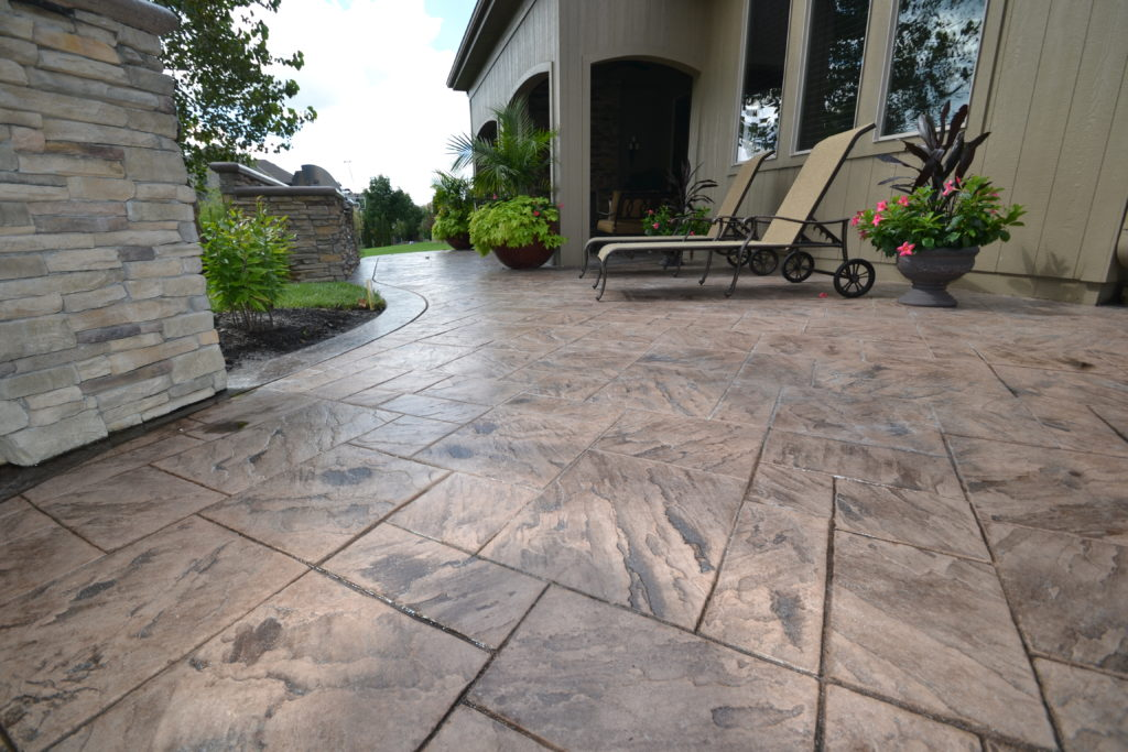 Stamped Concrete Patio with Outdoor Fireplace, Grill,  and Seat wall.