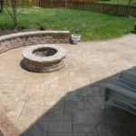 Aesthetic Concrete Designs can make your outdoor living space beautiful with a custom stamped concrete fire pit and seat wall.