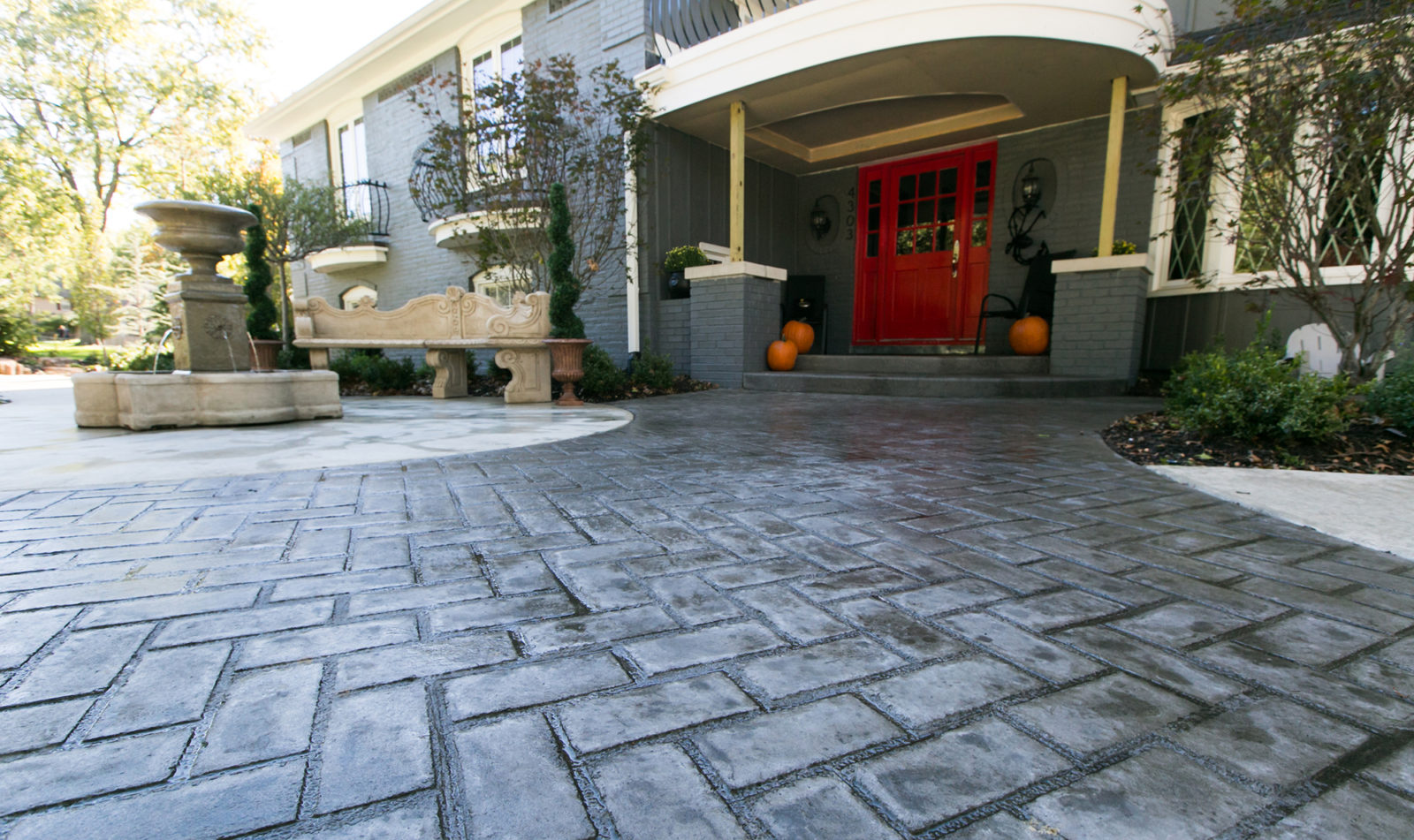 Aesthetic Concrete Designs creates decorative concrete like stamped concrete gray brick for a circular driveway.