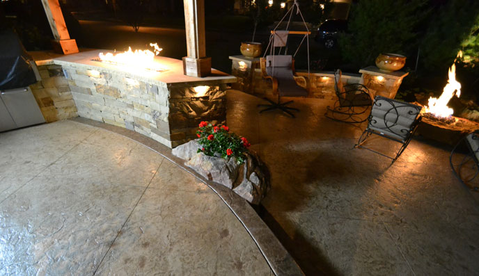 Make your outdoor space comfortable and beautiful with a stamped concrete patio, custom fireplace and seat walls from Aesthetic Concrete Designs.
