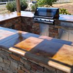 Outdoor Kitchen with stained concrete counter tops and pergola.
