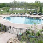 Colored concrete pool deck with waterfall and pool coping.