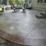 Stamped patio in a free form bordered with dark stain and round steps.